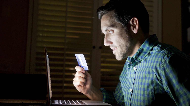 Mann sitzt mit seiner Kreditkarte vor dem Laptop