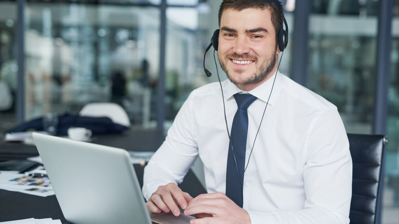 Ein lächelnder Kundendienstberater sitzt mit Laptop und Headset am Schreibtisch