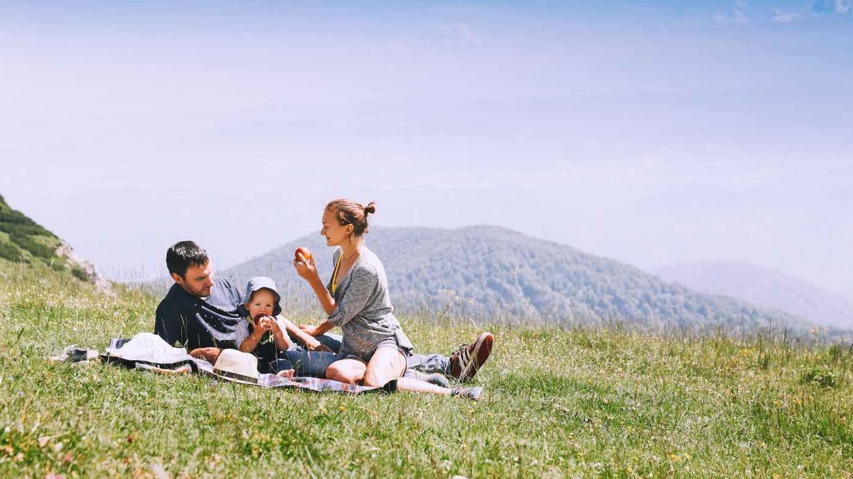 Ein Familie breitet eine rot-weiß karierte Picknickdecke im Park aus