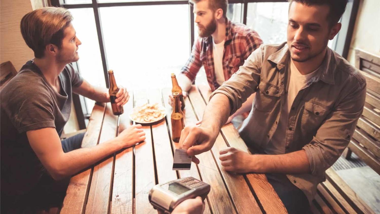 Studenten in der Kneipe, einer zahlt per Kreditkarte die Rechnung
