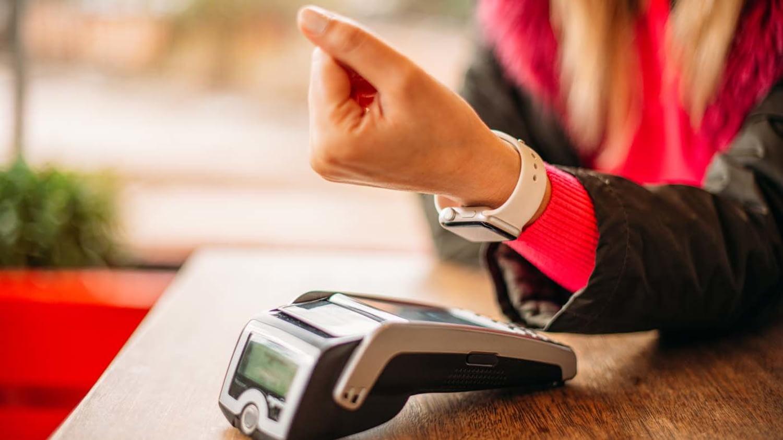 Frau hält den Arm mit ihrer Smartwatch an ein Bezahlterminal