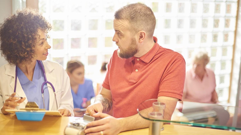 Ein junger Mann wirkt im Gespräch mit seiner Ärztin überrascht