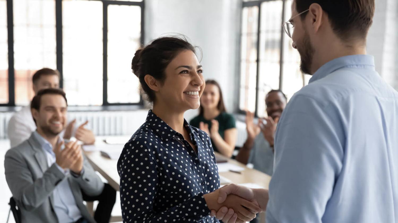 Frau wird an ihrem ersten Arbeitstag im Unternehmen von ihren neuen Kollegen begrüßt