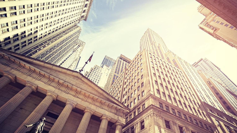 Blick von unten auf die Federal Hall an der New Yorker Wall Street mit umstehenden Hochhäusern