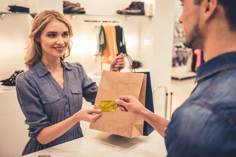 Verkäuferin in einer Boutique übergibt einem Kunden die Ware, die er mit Kreditkarte bezahlt hat