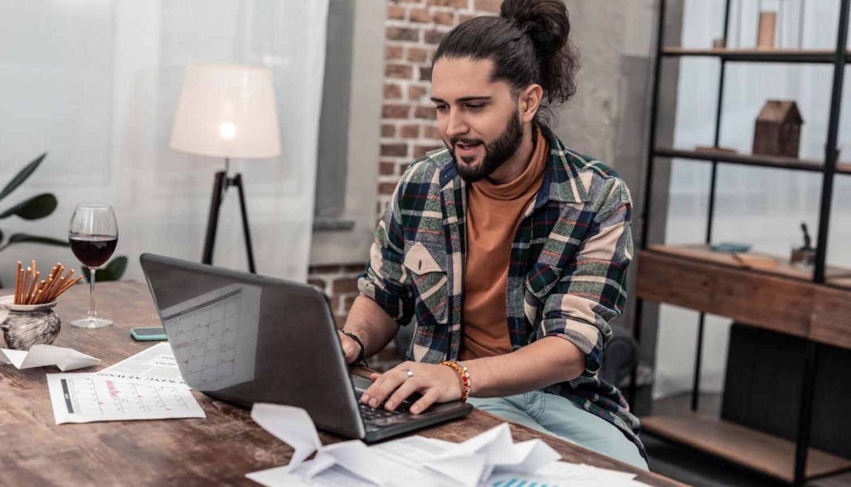 Ein junger Mann arbeitet an seinem Laptop, während er Wein und Salzstangen genießt und Papiere auf seinem Schreibtisch verstreut sind