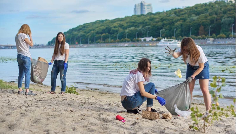 Junge Frauen sammeln Müll von einem Flussufer