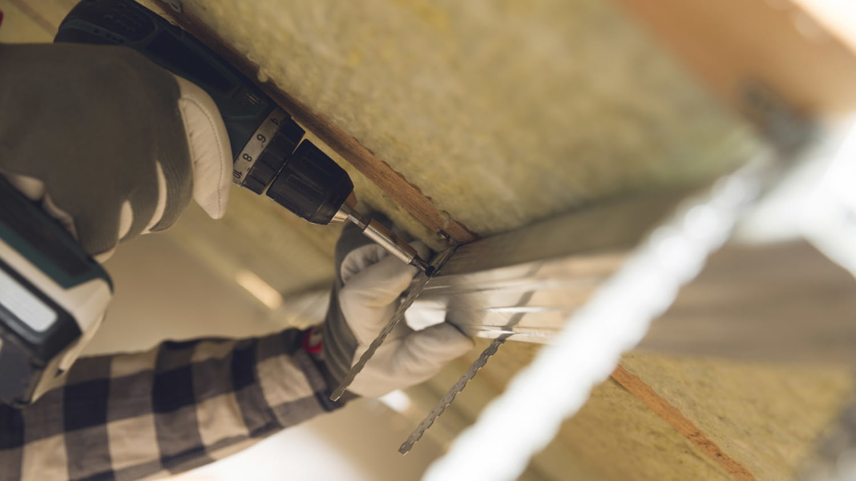 Detailaufnahme der Hände eines Handwerkers beim Anbringen einer Dachdämmung