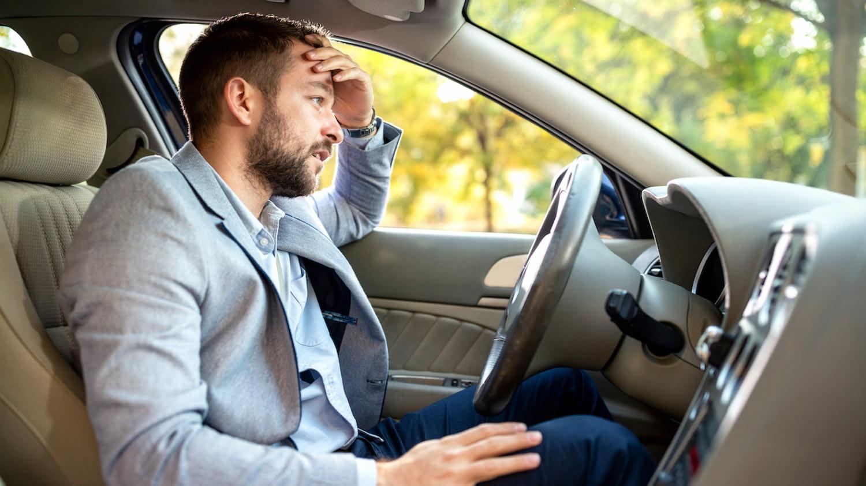 Mann sitzt hinter dem Steuer seines stehenden Autos und fasst sich verwundert an den Kopf