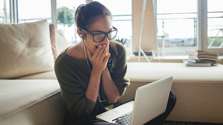 Freudig aufgeregte Frau mit Laptop auf dem Schoß schlägt die Hände vor ihrem Gesicht zusammen