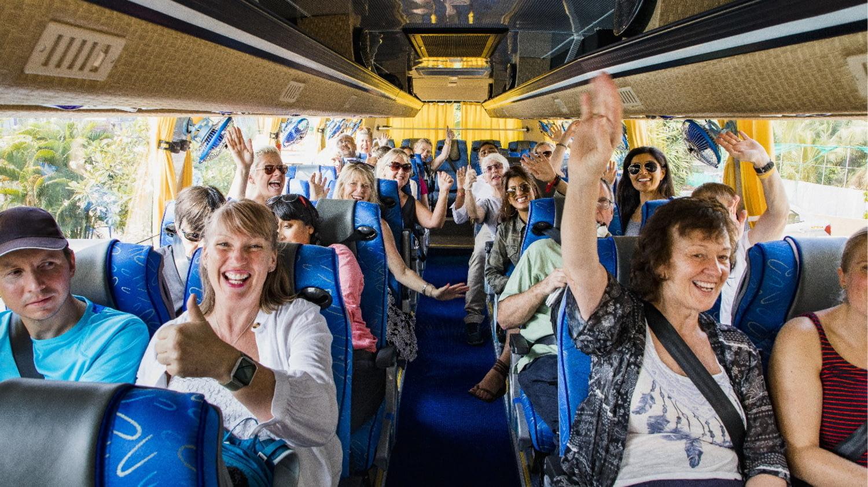 Eine Gruppe Urlauber sitzt gut gelaunt im Reisebus