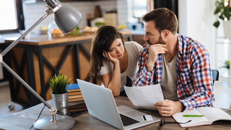 Ein junges Paar sitzt vor einem Laptop und vergleicht Papiere