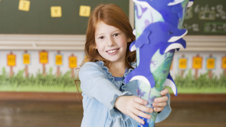 Erstklässlerin hält große Schultüte, die mit Delphinen dekoriert ist