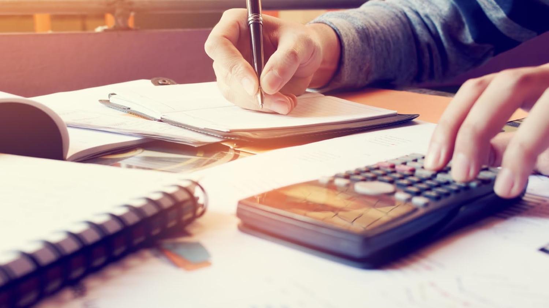 Person schreibt mit der einen Hand auf einem Notizblock und tippt mit der anderen Hand auf einem Taschenrechner