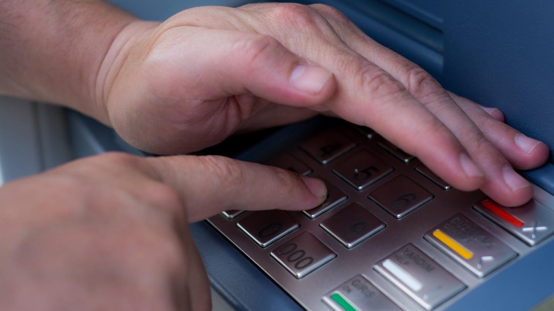 Mann gibt seine PIN am Geldautomaten ein
