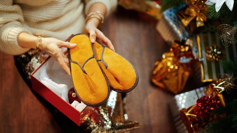 Elegant gekleidete Frau fördert beim Auspacken ihres Weihnachtsgeschenks ein Paar merkwürdige Hausschuhe zutage