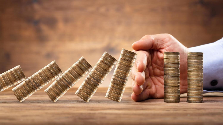 Eine Hand schützt zwei Stapel mit Münzen vor dem Dominoeffekt durch andere, fallende Stapel