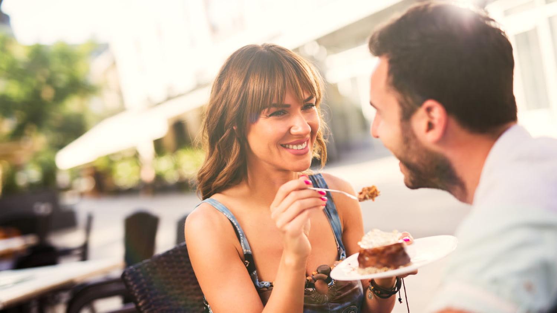 Fröhliche junge Frau füttert ihren Freund in einem Café mit Kuchen
