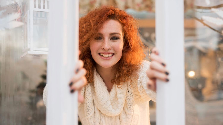 Eine Frau im Pullover öffnet lächelnd die beiden Flügel eines großen Fensters
