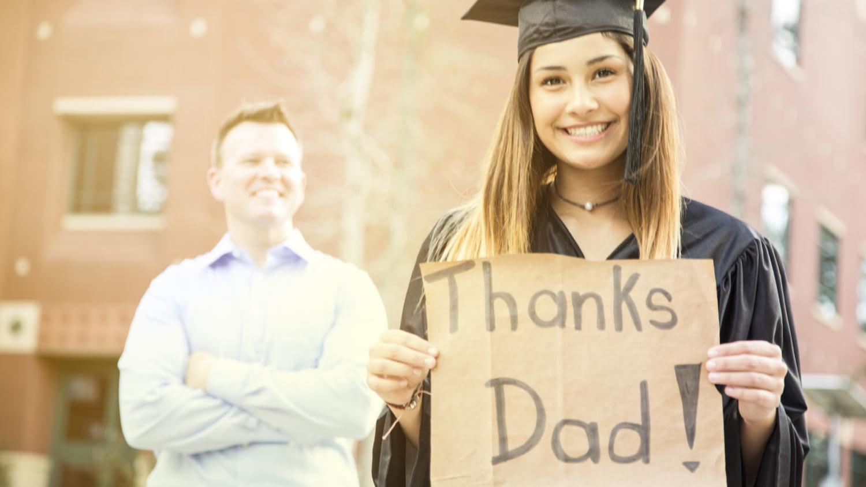 """Studentin hält bei ihrer Abschlussfeier ein Schild mit der Aufschrift """"Thanks Dad"""", im Hintergrund der stolze Vater"""