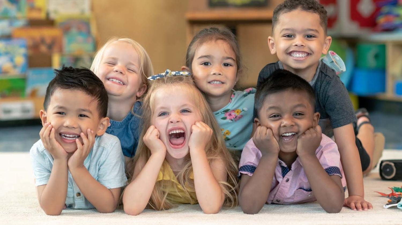 Eine Gruppe Kindergartenkinder strahlt auf dem Bauch liegend in die Kamera