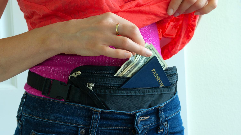 Frau zieht Geld und Pass aus einer Bauchtasche, die sie unter Ihrem T-Shirt trägt