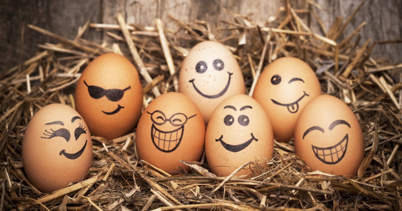 Verschiedene braune Eier, bemalt mit Smileys und anderen Gesichtern