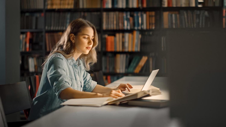 Junge Frau in der Bibliothek arbeitet an ihren Laptop