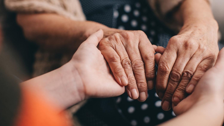 Eine junge Frau hält die Hände einer älteren Frau.