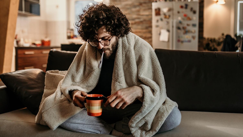 Ein junger erkälteter Mann sitzt matt in seiner Wohnung