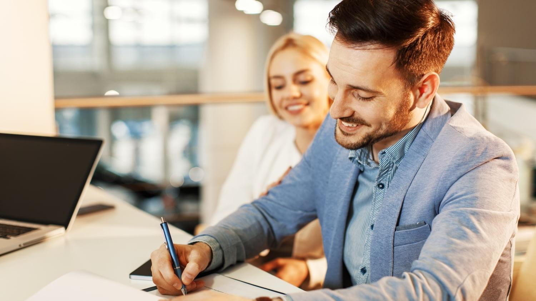 Ein Pärchen sitzt an einem Tisch in einer Bank, der Mann unterschreibt das Formular eines Freistellungsauftrags