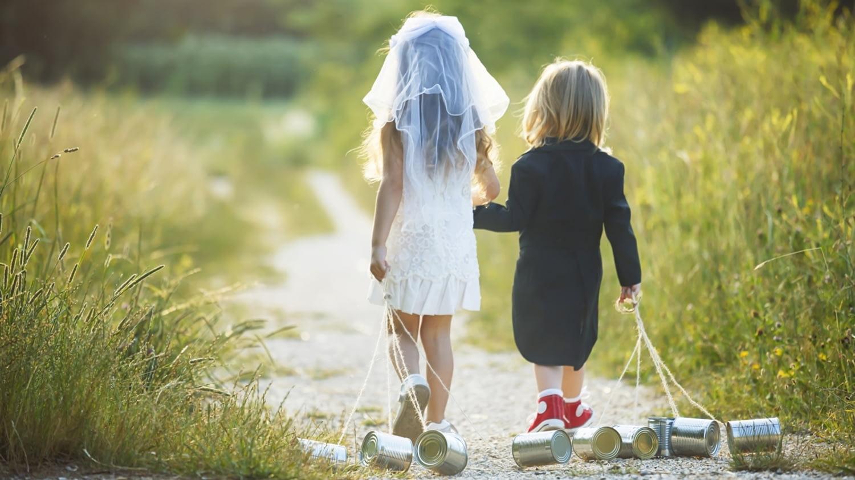 Kleine Kinder laufen als Braut und Bräutigam verkleidet durch eine Wiese.