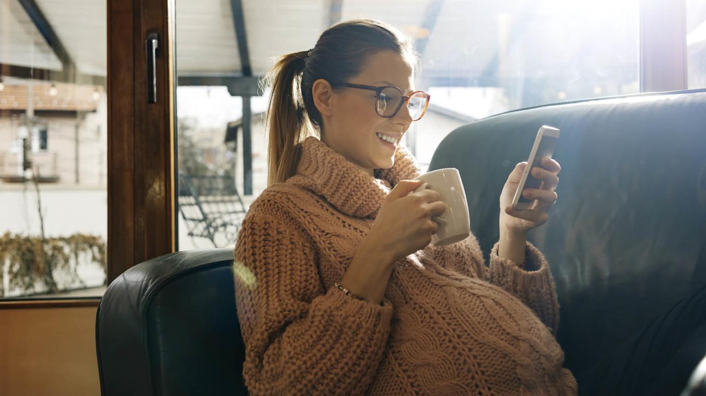 Entspannte Hochschwangere mit Kaffeetasse und Smartphone auf dem Sofa