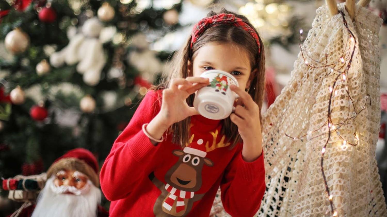 Junges Mädchen im Weihnachtspullover trinkt aus einem Becher