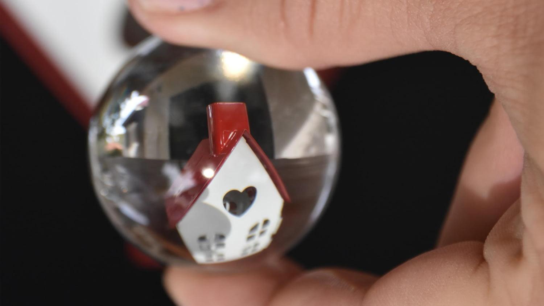 Glaskugel, in der ein kleines Modell-Häuschen zu sehen ist