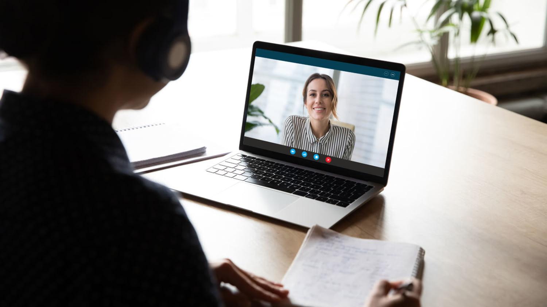 Person sitzt mit Headset vor dem Laptop und hält mit einer anderen Person eine Videokonferenz ab