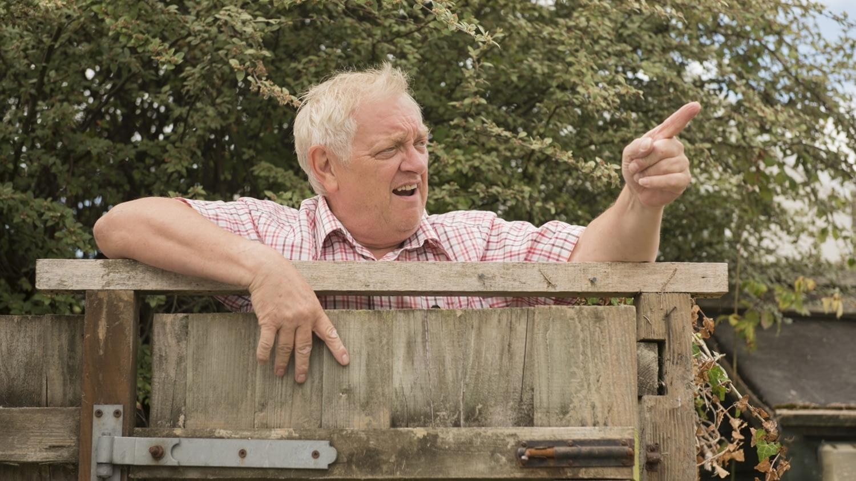 Ein älterer Mann schimpft über den Gartenzaun mit seinen Nachbarn