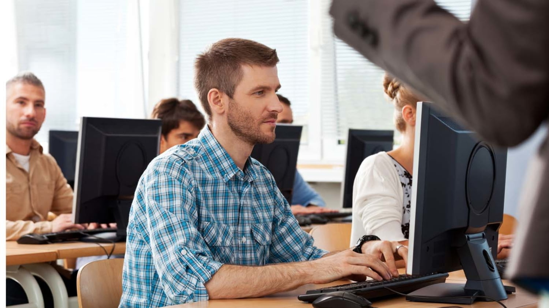 Erwachsene Schüler sitzen in einem Klassenraum an Computer-Arbeitsplätzen während ein Dozent spricht