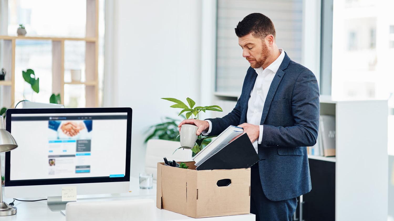 Ein Mann packt im Büro seine Sachen vom Schreibtisch in einen Karton