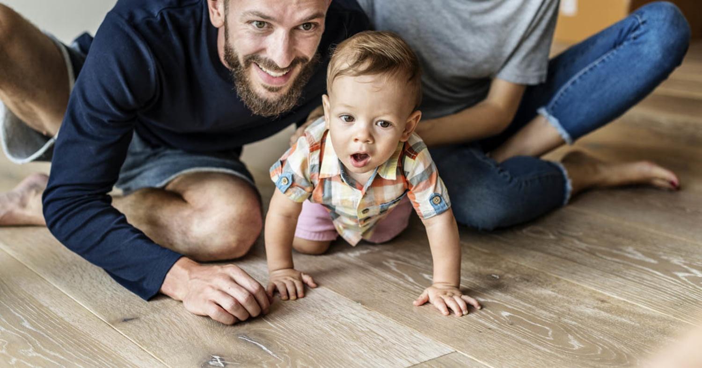 Junges Paar spielt mit Kleinkind auf dem Fußboden