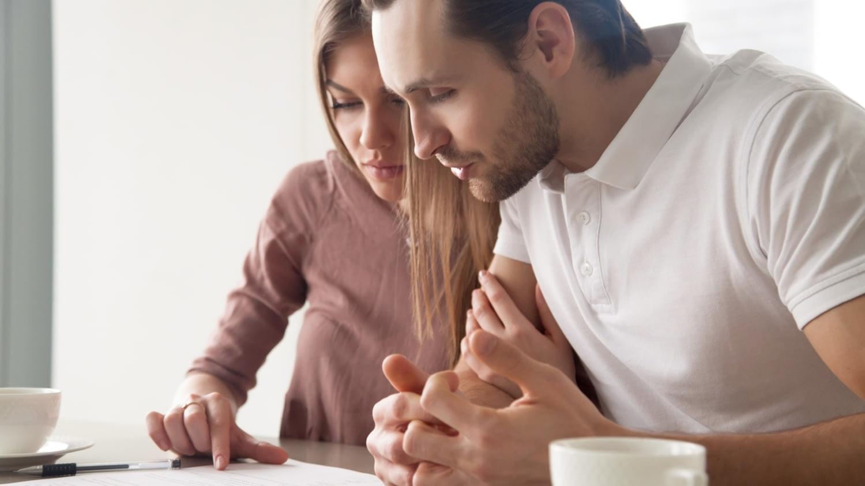 Ein junges Paar sitzt an einem Tisch und liest gemeinsam in einem Vertrag.