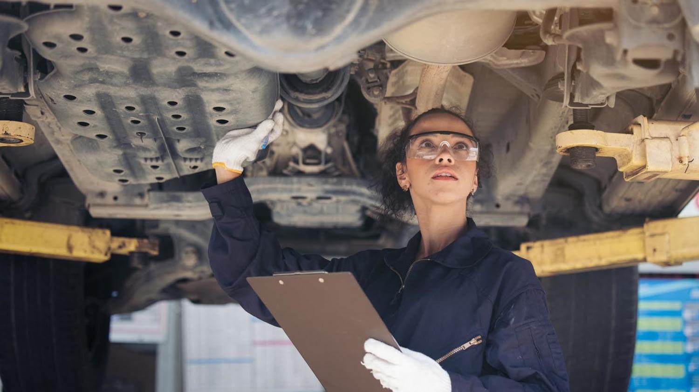 Mechanikerin inspiziert die Unterseite eines Autos