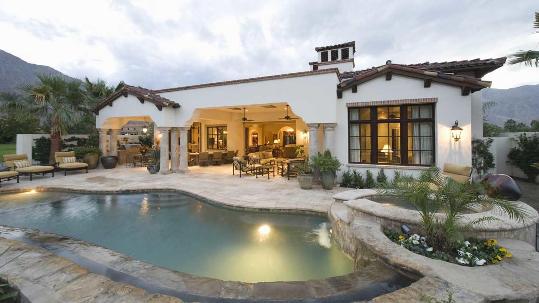 Ein weißes, erleuchtetes Haus steht in einer Bergkulisse, im Vordergrund ist ein Swimmingpool zu sehen