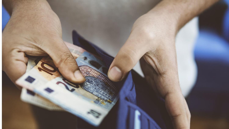 Detailaufnahme eines Portemonnaies, aus dem ein junger Mann Geld nimmt