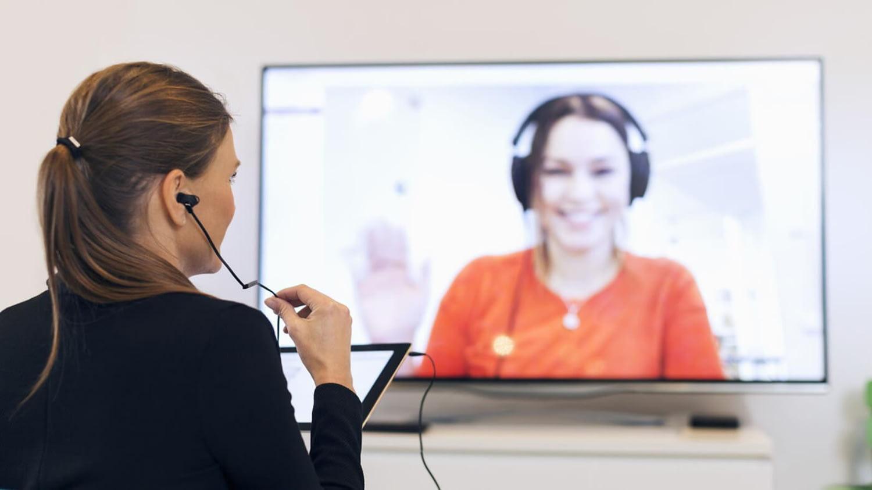 Frau blickt auf einen großen Bildschirm, auf dem ihr eine andere Frau zuwinkt