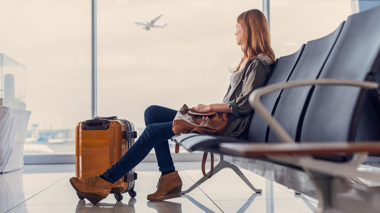 Junge Frau mit Rollkoffer schaut aus der Abflughalle einem startenden Flugzeug hinterher.
