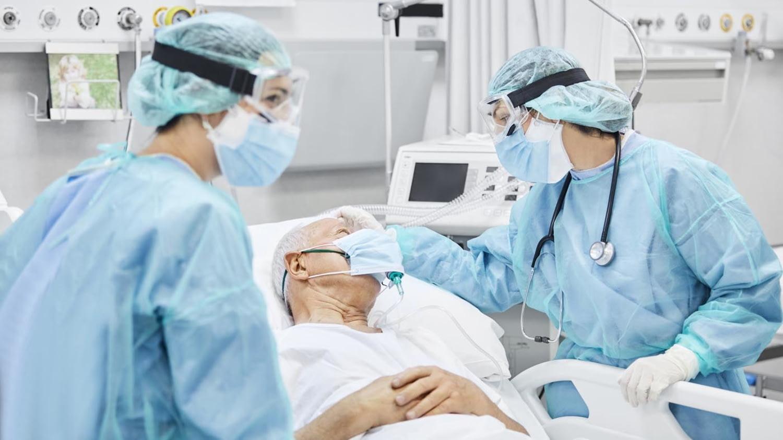 Älterer Mann wird im Krankenhaus von Schwestern in Schutzkleidung betreut