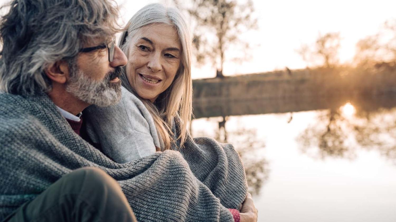 Ein älteres Paar sitzt in Decken gehüllt an einem Fluss und genießt die Abendstimmung