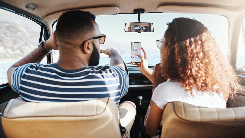 Pärchen sitzt im Auto, er fährt, während sie ihm das Smartphone hinhält, auf dem die Route zu sehen ist