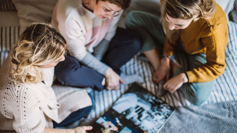 Zwei junge Frauen und eine ältere sitzen auf einem Bett und blättern ein Fotoalbum durch